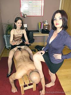 Two office girls are working as a team dominating bald slave with their sexy legs: barefoot and wearing high heel shoes
