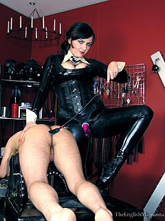 Domme in rubber catsuit is preparing nude male for severe caning punishment