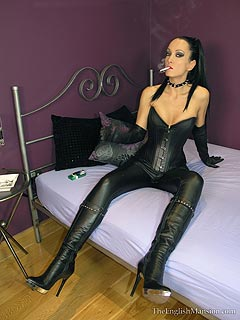 Gorgoeus dominatrix is wearing tight black leather, smoking a cigarette and facesitting naked slave