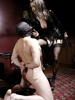 Dominatrix is giving slave a chance to lubricate the strapon cock she is going to fuck him with