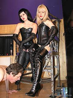 Two femdom girls are both wearing leather knee boots when training nude male with bondage, ass whipping and forced cock milking