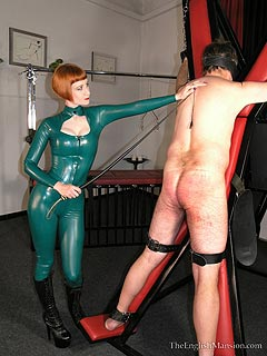Latex lady is having naked male strapped to BDSM cross and whipped to bruises