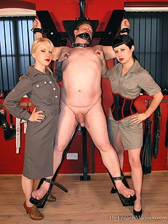 Gagged male is tied naked to the BDSM cross by a couple of military bitches