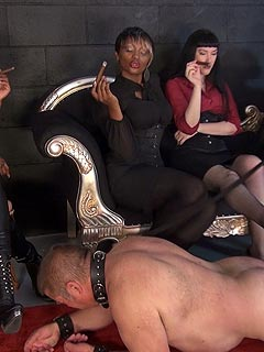 A company of smoking ladies are putting hot ash all over exposed male slave cock and balls