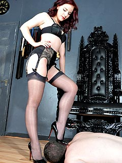 Goddess with perfect legs in black stockings giving slave a chance to worship her feet in high heels and barefoot