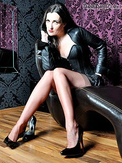 Closeup view of a leggy dominatrix changing high heel shoes and loving the way her legs look in seamed nylon stockings