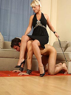 Riding crop and a pair of high heels are making femdom slave complete when sexy blond is controlling him all over