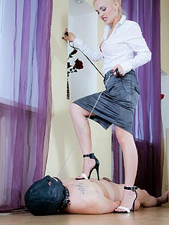 Elegant office lady is having her personal foot slave to play with: trampling him at will