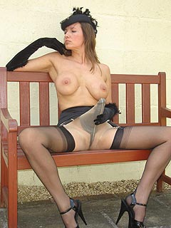 Femdom lady is looking very sexy topless, wearing nylons and having a strap-on toy underneath