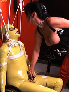 Erotic MILF is playing with her own personal bondage doll she made out of submissive man dressed up in rubber